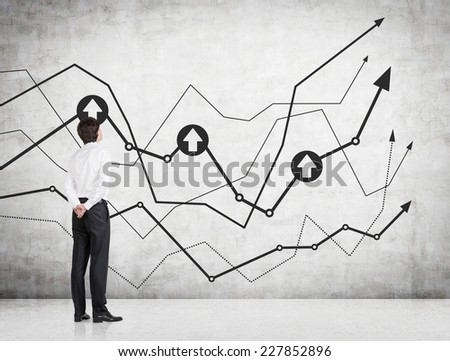 Businessman is standing in front of a chart on the concrete wall.  - stock photo
