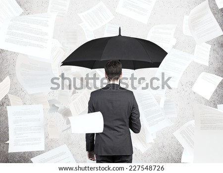 businessman is standing under the papers rain. - stock photo