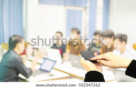 Businessman is using mobile phone over blurred people during training in a room