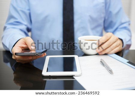 Businessman is using smart phone and reading email on tablet pc and holding cup of coffee with documentation od desk