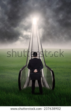 Businessman is walking up the escalator from the green field - stock photo