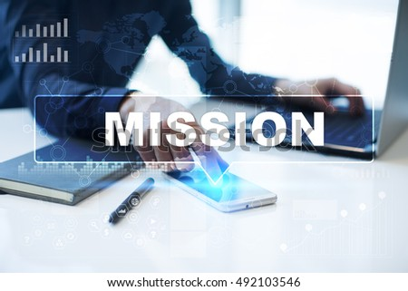 "Businessman is working in office, pressing button on virtual screen and selecting ""Mission"". Business concept."