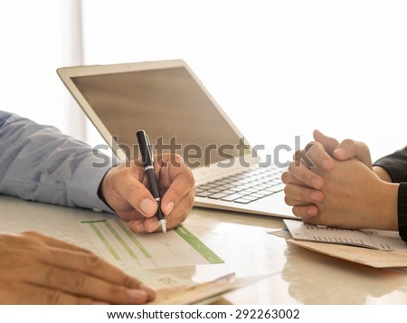 Businessman is writing a deposit slip. - stock photo
