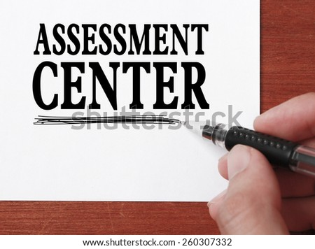 Businessman is writing Assessment center text on white paper. - stock photo