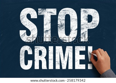 Businessman is writing Stop Crime text on blue chalkboard. - stock photo