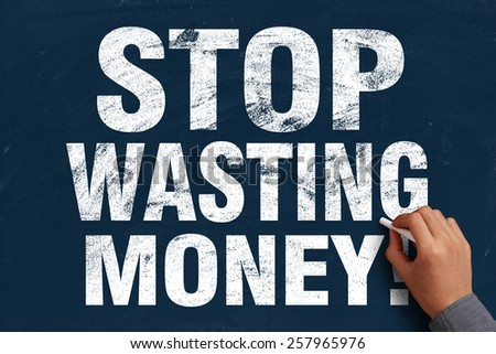 Businessman is writing Stop Wasting Money text on blue chalkboard. - stock photo