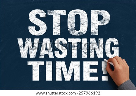 Businessman is writing Stop Wasting Time text on blue ...