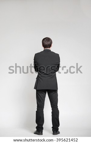 Businessman isolated on white and looking on empty wall - stock photo