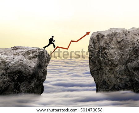 businessman jump across challenge with increasing graph
