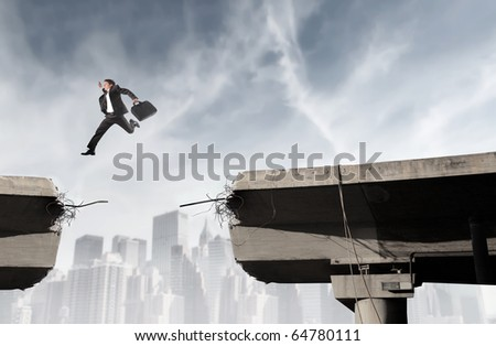 Businessman jumping from a part of a broken bridge to another - stock photo