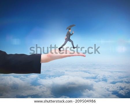 Businessman jumping holding an umbrella against blue sky over clouds at high altitude