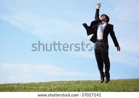businessman jumping on grass