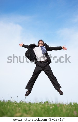 Businessman jumping on the meadow