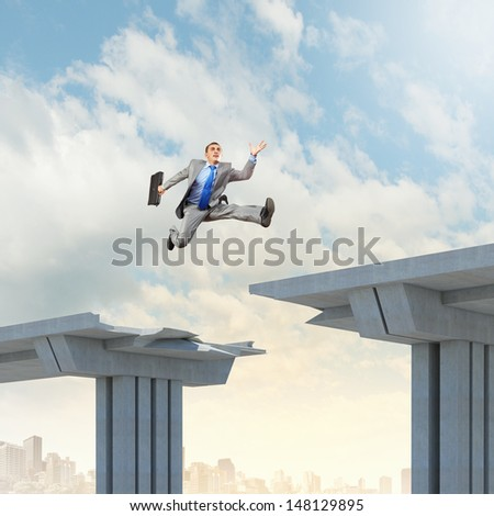 Businessman jumping over a gap in the bridge as a symbol of bridge