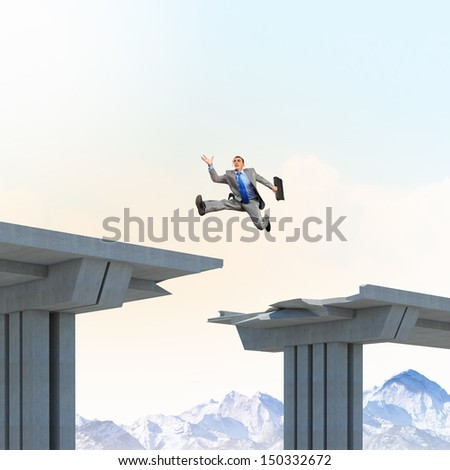 Businessman jumping over a gap in the bridge as a symbol of bridge - stock photo