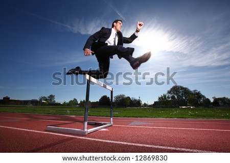 Businessman jumping over hurdle - stock photo