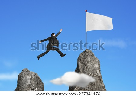 businessman jumping over mountain peak to blank flag with natural sky cloud background - stock photo