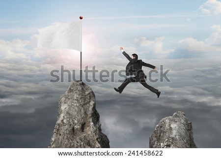 businessman jumping over mountain peak to blank flag with natural sunlight cloudscapes background - stock photo