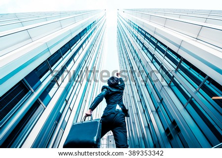 Businessman jumping over the camera, low angle, building background - stock photo