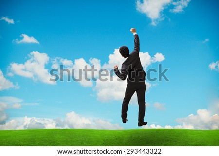 Businessman jumping punch into the air,Celebrating success concept