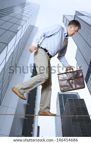 Businessman keeping his balance on a rope over a big city - stock photo