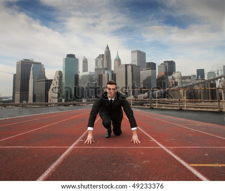 Businessman kneeling on a starting grid with cityscape on the background - stock photo