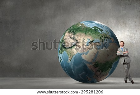 Businessman leaning on huge Earth planet. Elements of this image are furnished by NASA - stock photo