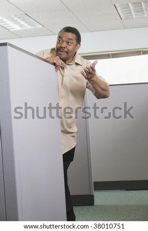 Businessman leaning over a cubicle to talk his neighbor. - stock photo