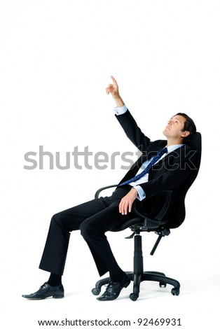Businessman leans back on his office chair and points up into the air, trying to visualize something - stock photo