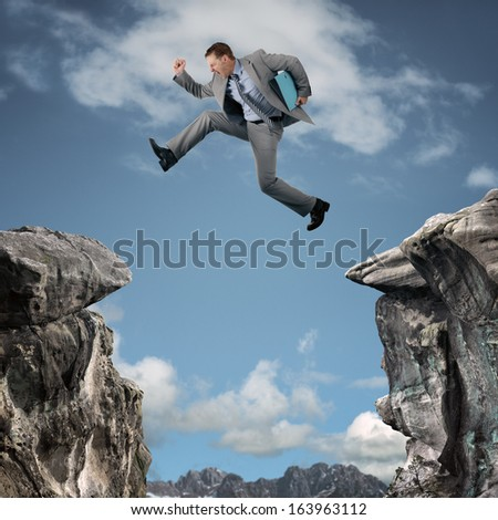 Businessman leap of faith concept for business adversity, risk or challenge - stock photo