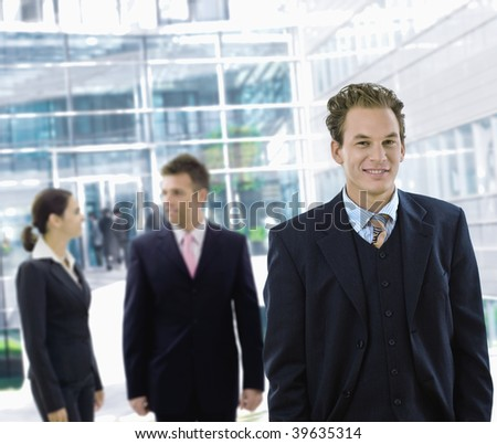 Businessman leaving office building aong other businesspeople in the background. - stock photo