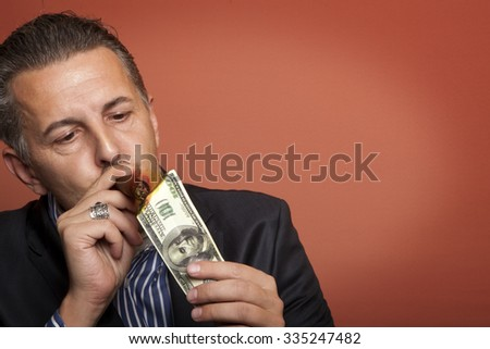 Businessman lighting cigar with 100 dollar bill - stock photo