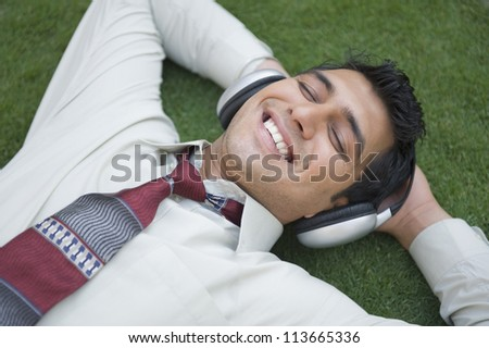 Businessman listening to music and smiling - stock photo