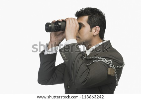 Businessman locked in chains and looking through binoculars - stock photo