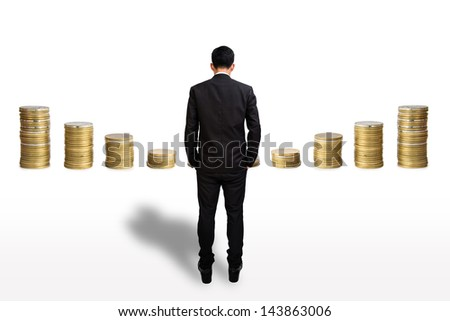 Businessman look at coins pile