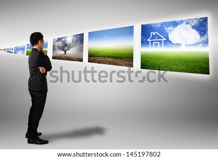 Businessman look different natural images on technology - stock photo