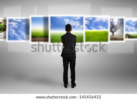 Businessman look different natural images on technology,digital screen - stock photo