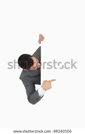 Businessman looking around the corner and pointing against a white background