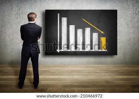 businessman looking at a diagram showing a declining graph - stock photo