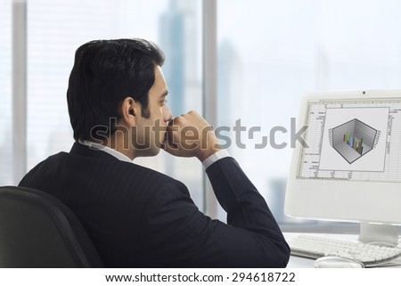 Businessman looking at a graph on his computer - stock photo