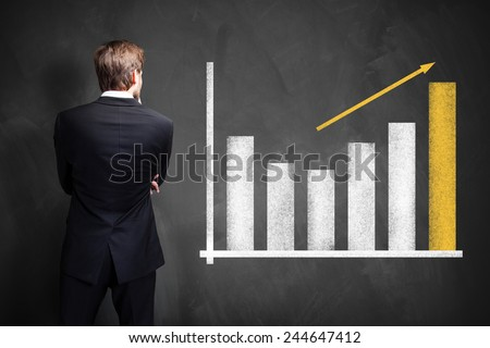 businessman looking at a growing info graph - stock photo