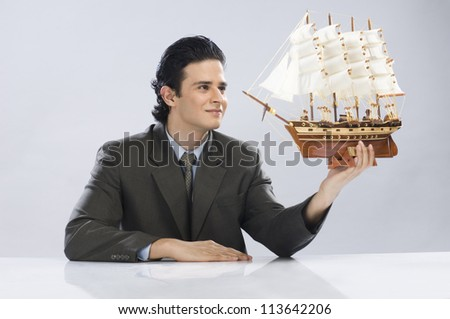 Businessman looking at a sailing ship - stock photo
