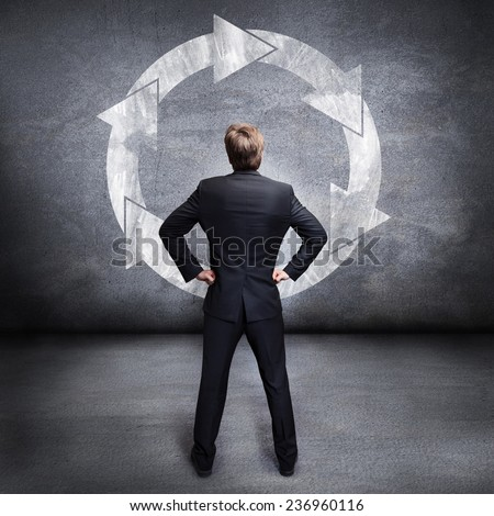 businessman looking at a wall with a loop sign - stock photo