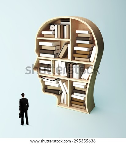 businessman looking at book shelf in form of head - stock photo