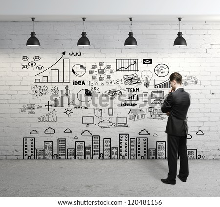businessman looking at business concept on wall - stock photo