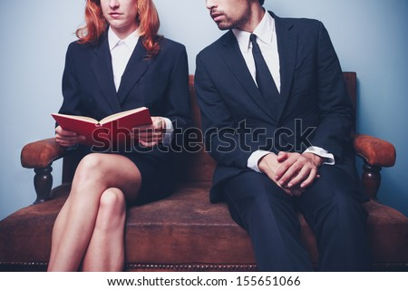 Businessman looking at businesswoman's book - stock photo