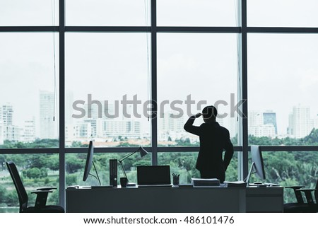 Businessman looking at city through the office window