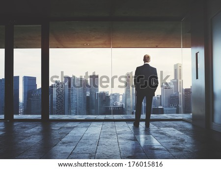 Businessman looking at city through window