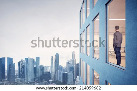 Businessman looking at city through window - stock photo