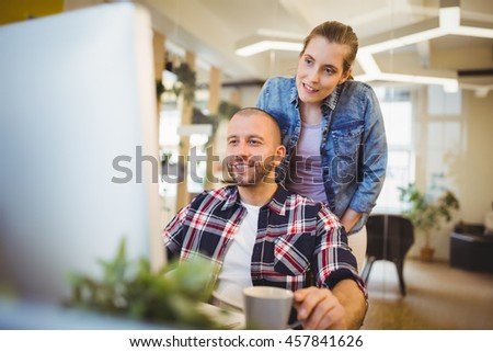 Businessman looking at computer while working with female colleague in creative office - stock photo